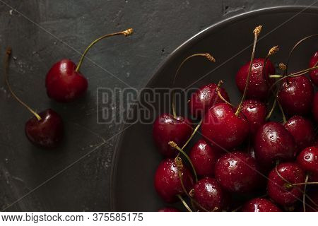Closeup On Many Ripe Bright Cherries With Water Drops In Brown Bowl And Two Berries Next To It On Da