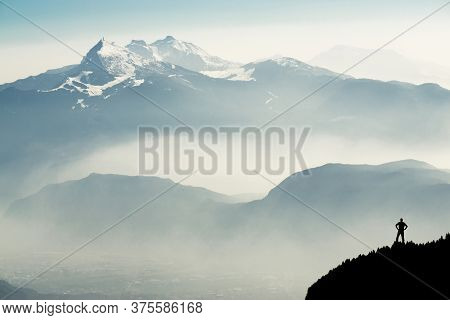 Man Reaching Summit Enjoying Amazing Sunrise In The Mountains. Backlight Sunlight With Beautiful Len