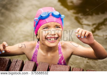 Young Small Tired 9 Years Old Girl Swimmer On Finish Line After Open Water Competition For Children.