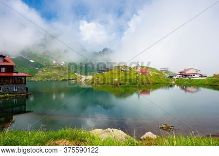 Clouds Above Balea Lake In Romania. Stunning Summer Landscape In Fagaras Mountains. Scenery Reflecti
