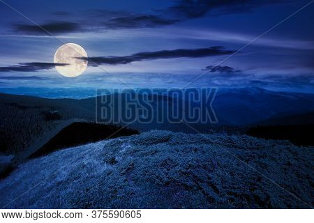 Hills And Valley Of Mountain Landscape At Night. Clouds On The Deep Blue Sky. Beautiful Scenery Of C