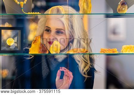 A Young, Beautiful, Blonde Woman Looks At Amber Jewelry At A Jewelry Store. View Through The Window