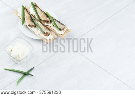 Fresh Summer Healthy Appetizer Of Whole Grain Crisps Breads With Sprats Preserves, Green Onion, Crea