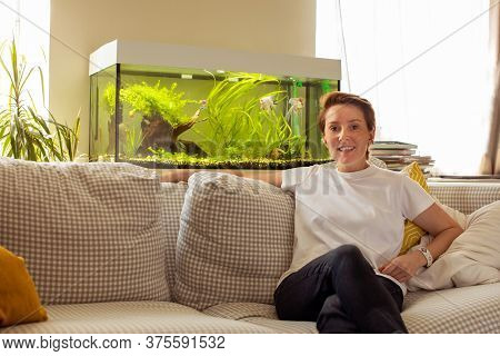 Smiling Female In Casual Wear Resting With Arms Outstretched And Legs Crossed On Comfy Checkered Sof