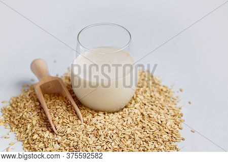 Vegan Non Dairy Alternative Oat Milk In Glass. Oat Cereal In Wooden Spoo On Stone Table. Concept Of