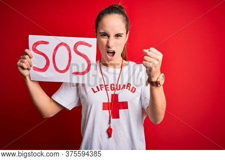 Lifeguard woman wearing t-shirt with red cross and whistle holding banner with sos message annoyed and frustrated shouting with anger, crazy and yelling with raised hand, anger concept