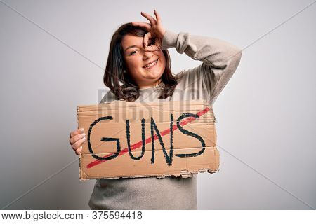 Plus size woman holding stop guns cardboard banner warning about violence with happy face smiling doing ok sign with hand on eye looking through fingers