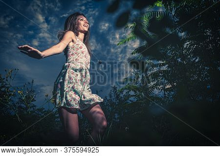 Jolly Girl Dancing Outdoors In Summertime In Tall Grass. She Is Dressed In Summer Dress And Dancing