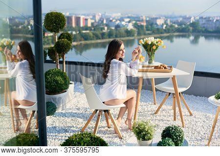 Young Woman In White Shirt With Bare Legs Is Enjoying Sunshine At Breakfast On Terrace Overlooking L