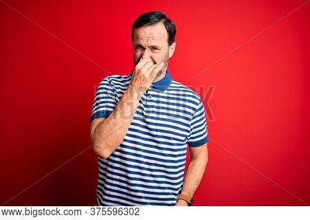 Middle age hoary man wearing casual striped polo standing over isolated red background smelling something stinky and disgusting, intolerable smell, holding breath with fingers on nose. Bad smell