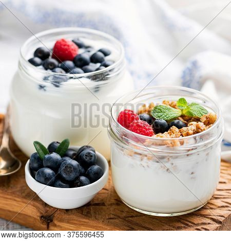 Greek Yogurt With Granola And Berries In A Jar. Healthy Yogurt Snack With Crunchy Oats Granola And S