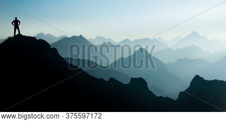 Man Reaching Summit After Climbing And Hiking Enjoying Freedom And Looking Towards Mountains Silhoue