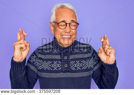 Middle age senior grey-haired man wearing glasses and winter sweater over purple background gesturing finger crossed smiling with hope and eyes closed. Luck and superstitious concept.