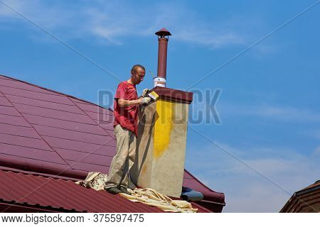 Painting With A Brush On The Roof, Work Of A Painter On The Roof, A Man Paints A Brush Yellow Color