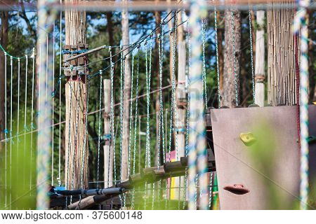 Adventure Climbing On High Wired Park. Forest Adventure Park Among Pine Trees.