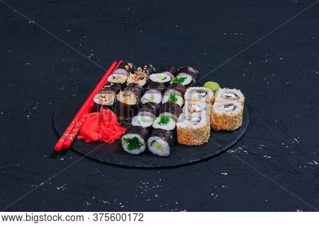 Sushi Rolls And Maki On A Black Plate, Japanese Food, Black Dark Background, Asian Cuisine