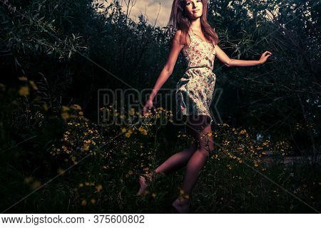 Happy Girl. A Young Girl Wears A Light Summer Dress And She Dances In High Grass In The Night