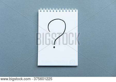 Notebook With The Schedule Shoot From The Top. Spiral Notebook Blue Background. Question Mark Writte