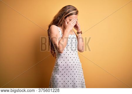 Young beautiful blonde woman on vacation wearing summer dress over yellow background with sad expression covering face with hands while crying. Depression concept.