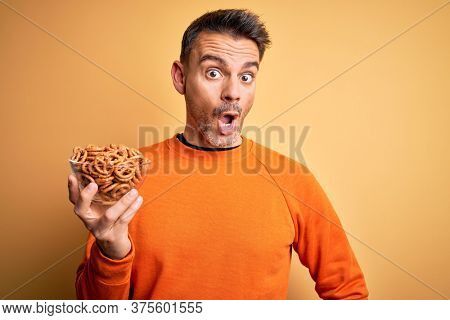 Young handsome man holding bowl with german baked pretzels over yellow background scared in shock with a surprise face, afraid and excited with fear expression