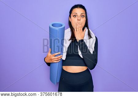 Young beautiful brunette sporty woman using sport towel hoding mat to do yoga covering mouth with hand, shocked and afraid for mistake. Surprised expression