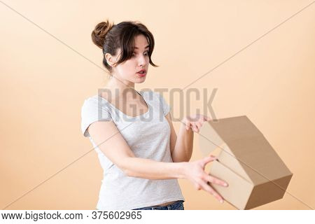 The Girl With The Gathered Hair In Bewilderment Opens A Cardboard Box And Looks With Curiosity At It