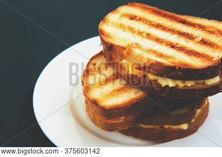 Grilled Toast Sandwich With Egg On A White Plate On A Dark Background. Toasted Breads For Breakfast.