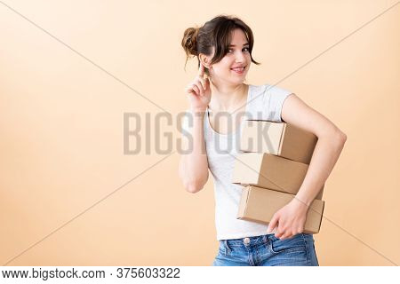 Girl With A Smile Eavesdrops With Boxes In Her Hands. The Courier Is Always Ready To Listen. Girl On