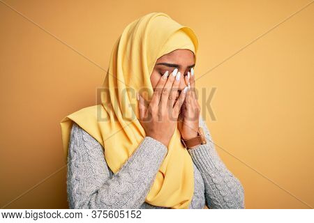 Young beautiful african american girl wearing muslim hijab over isolated yellow background rubbing eyes for fatigue and headache, sleepy and tired expression. Vision problem