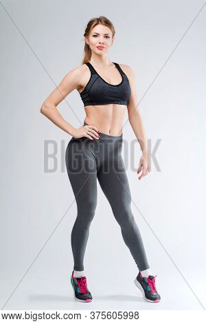 Young happy fitness girl with sporty body drink water at studio on a white background. Beautiful fit
