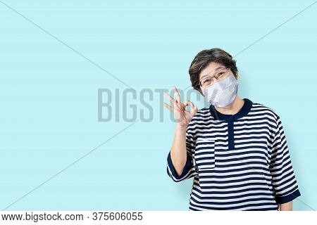 Portrait Of Happy Senior Asian Woman Wear Face Mask And Gesture Or Showing Hand Ok And Looking At Ca
