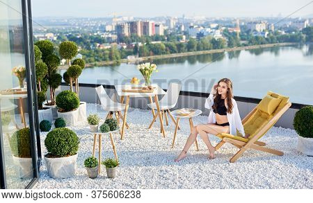 Slender Girl In Black Lingerie And White Shirt Is Having Breakfast On Balcony With Bouquet Of Tulips