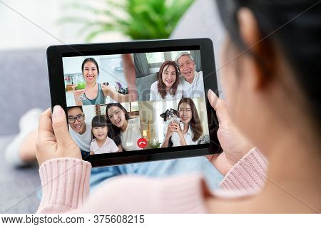 Asian Woman Talking With Family On Video Call Webcam In Living Room At Home While Working From Home.