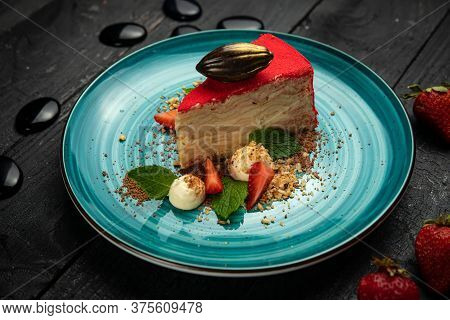 Napoleon Cake With Strawberries And Ice Cream On A Round Plate