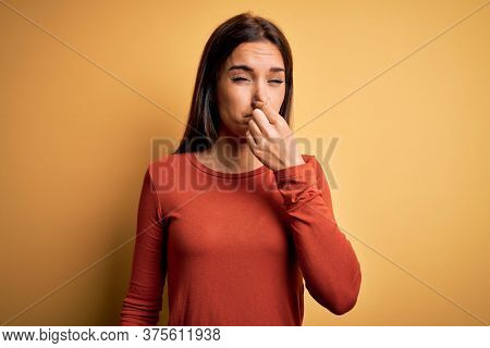 Young beautiful brunette woman wearing casual t-shirt standing over yellow background smelling something stinky and disgusting, intolerable smell, holding breath with fingers on nose. Bad smell