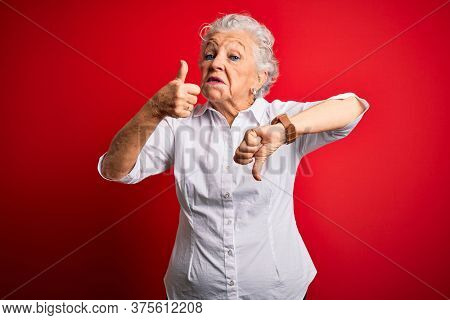 Senior beautiful woman wearing elegant shirt standing over isolated red background Doing thumbs up and down, disagreement and agreement expression. Crazy conflict