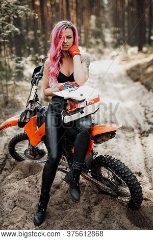 Beautiful Tattooed Hipster Girl With Bright Pink Hair Sitting On Her Motocross Bike In Woods