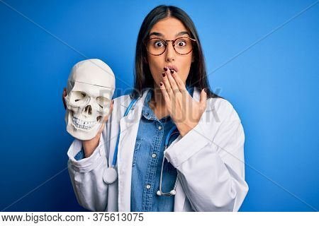 Young beautiful brunette doctor woman wearing coat holding human skull standing cover mouth with hand shocked with shame for mistake, expression of fear, scared in silence, secret concept