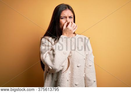Young beautiful woman with blue eyes wearing casual sweater standing over yellow background smelling something stinky and disgusting, intolerable smell, holding breath with fingers on nose. Bad smell