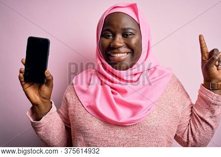 African american plus size woman wearing muslim hijab holding smartphone showing screen surprised with an idea or question pointing finger with happy face, number one