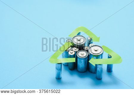 Used Aa And Proper Disposal Of Toxic To The Environment And Soil Batteries On A Blue Background. The