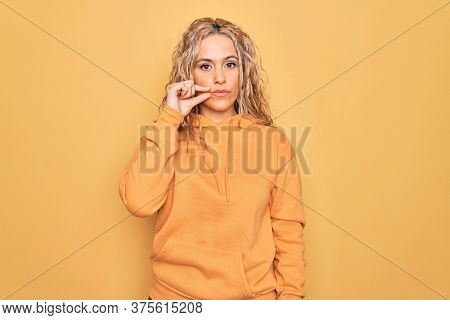 Young beautiful blonde sporty woman wearing casual sweatshirt over yellow background mouth and lips shut as zip with fingers. Secret and silent, taboo talking