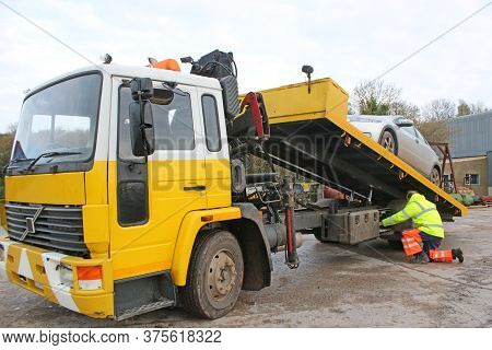 Man Loading Car On A Recovery Truck