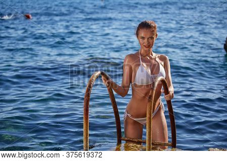 Portrait of young woman in white bikini on tropical beach looking at camera. Beautiful girl in swimwear with copy space. Summer vacation and tanning concept.