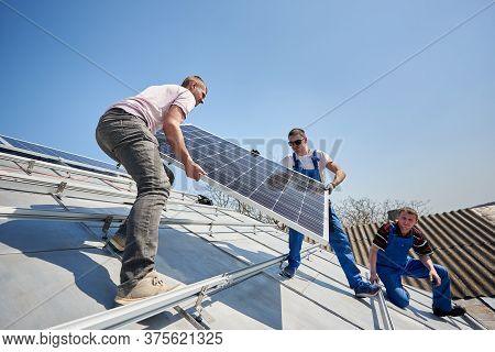 Male Engineers Installing Solar Photovoltaic Panel System. Three Electricians Lifting Blue Solar Mod