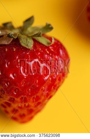 Close Up Strawberry At Yellow Background. Minimal Concept Of Harvesting Food.