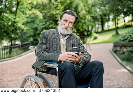 Handicapped Elderly Bearded Man Sitting In A Wheelchair In City Park Outdoors, Holding His Mobile Ph