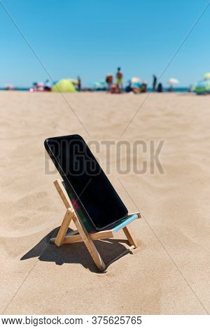 a black smartphone in a deck chair on the sand of the beach, depicting the digital detox concept, with unrecognizable people enjoying and the sea in the background