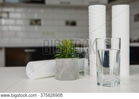 A Glass Of Clean Water With Osmosis Filter And Cartridges On White Table In A Kitchen Interior. Conc