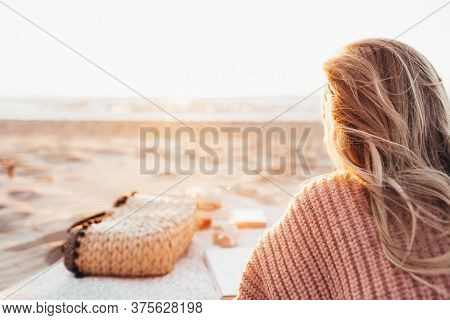 Young Blonde Woman Lying Alone On The Beach Or Ocean And Look At The Horizont. A Woman Dressed In A